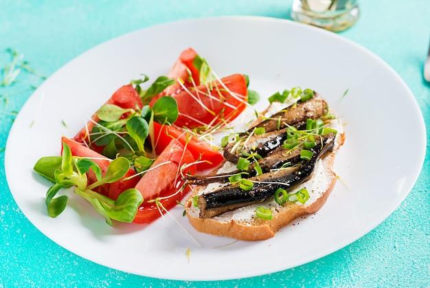 Сэндвич - сморреброд со шпротами и салатом из помидоров на белой тарелке