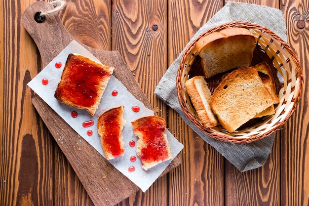 Sandwich of toast and jam drops on a cutting board