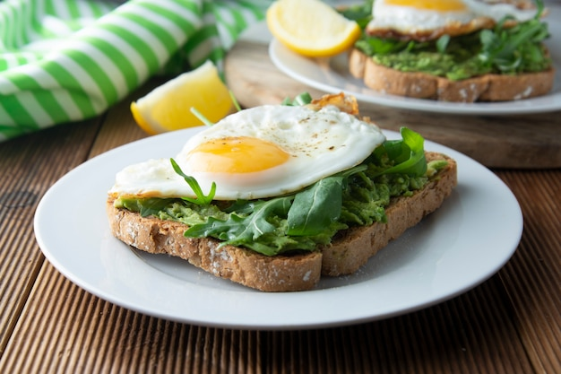 Sandwich toast with avocado and a fried egg on wood table. healthy food.