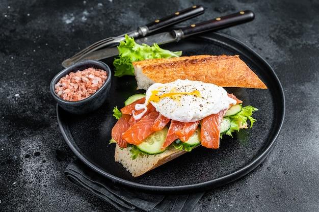 빵에 베네딕트 에그, 훈제 연어, 아보카도를 곁들인 샌드위치 토스트. 검은 배경. 평면도.
