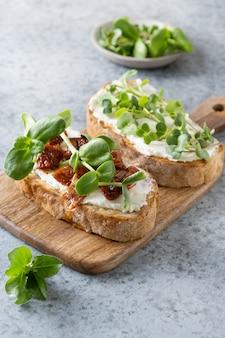 Sandwich on toast with fresh radish microgreen and cream cheese on grey. close up.