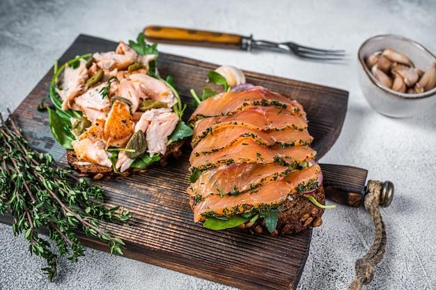 Сэндвич-тост с лососем горячего и холодного копчения, рукколой и сливочным сыром на деревянной доске. белый фон. вид сверху.