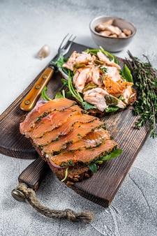 Сэндвич-тост с лососем горячего и холодного копчения, рукколой и сливочным сыром на деревянной доске