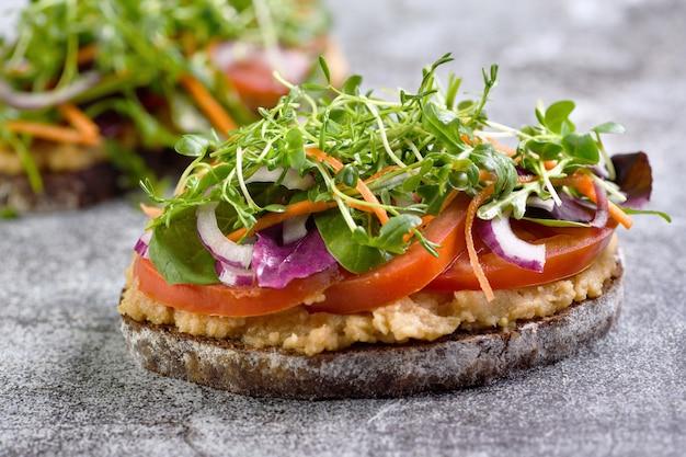 Поджаренный деревенский хлеб сэндвич с хумусом из нута, ломтиками помидора, микс салатом и микрозеленью
