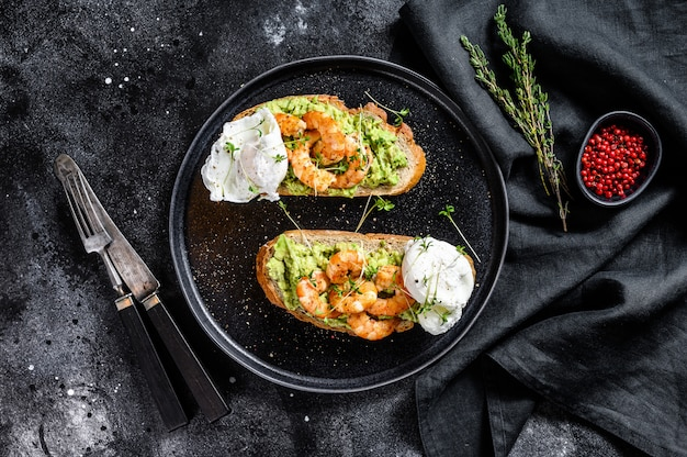 Sandwich topped with fresh prawns, shrimps on avocado with egg. a healthy food, scandinavian cuisine. black background. top view