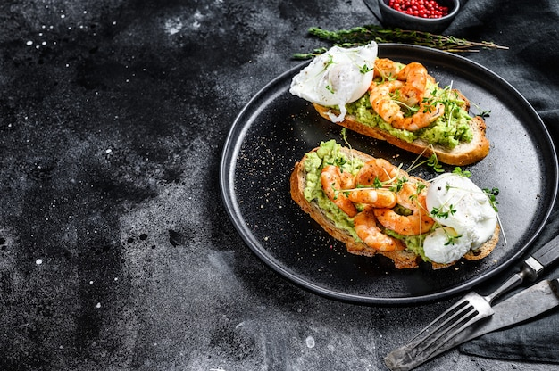 Sandwich topped with fresh prawns, shrimps on avocado with egg. a healthy food, scandinavian cuisine. black background.