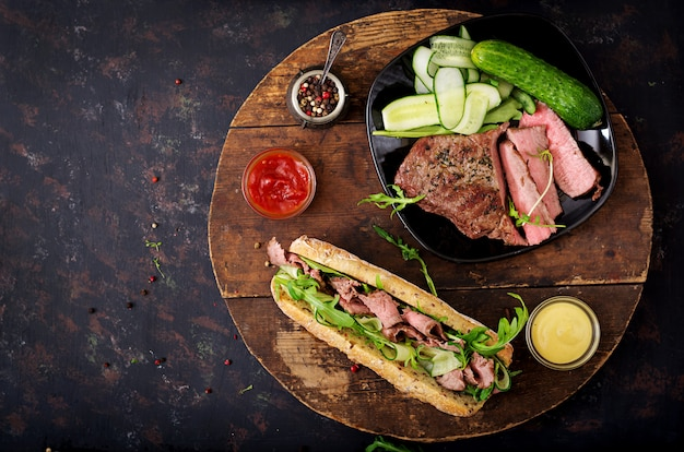Sandwich of whole wheat bread with roast beef, cucumber and arugula. .