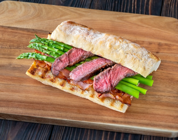 Сэндвич со спаржей и кусочками говяжьего стейка на деревянной доске