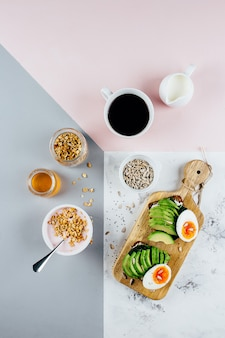 Sandwich with avocado and boiled eggs, yogurt with granola, cup of coffee over tricolor background
