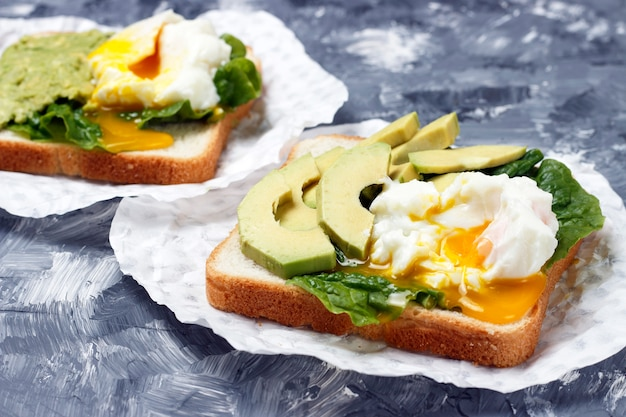 Sandwich with avocado and egg close-up, white and gray