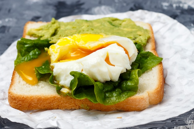 Sandwich with avocado and egg close-up