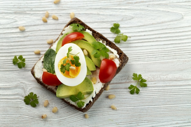Sandwich with avocado, egg, tomato, cheese, parsley, salad leaves