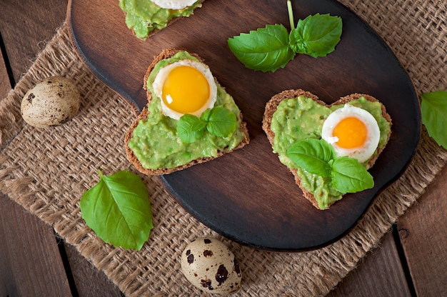 Sandwich with avocado paste and egg in the shape of heart