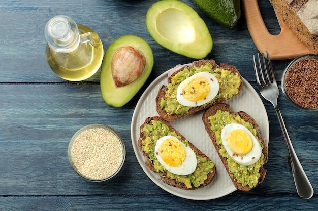 皿にアボカドのピューレと卵、青い木製のテーブルで調理するための材料が入ったサンドイッチ。上からの眺め