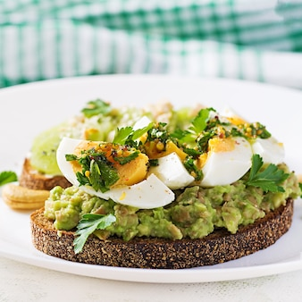 Sandwich with avocado puree, boiled eggs and sandwich cream cheese, kiwi, nuts