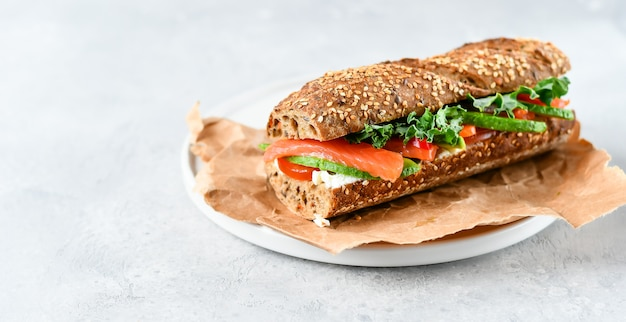 Sandwich  with avocado, salmon, cream cheese, tomatoes and lettuce leaves