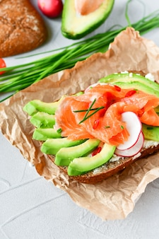Sandwich with avocado and salmon on a light background