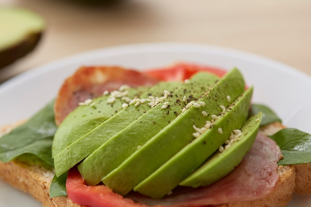 Sandwich with avocado slices and bacon