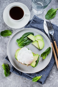 Sandwich with avocado, spinach and poached egg on whole wheat bread on plate on stone back