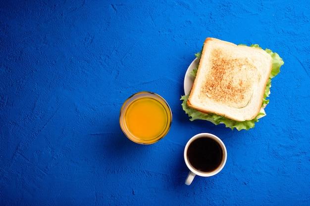 파란색 배경에 베이컨, 치즈, 허브를 넣은 샌드위치