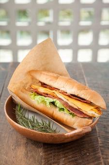 Сэндвич с беконом, ветчиной, яйцом и сыром чеддер