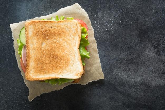 Sandwich with bacon, tomato, onion, salad on black