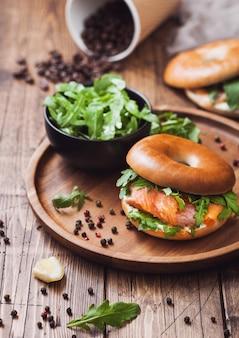 Сэндвич с бубликом и лососем, сливочным сыром и дикой рукколой в миске и кофейной чашке с фасолью на фоне деревянного стола