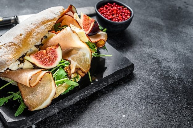 Sandwich with baguette, ham, fig, arugula and prosciutto meat