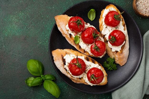 Сэндвич с запеченными помидорами черри, чесноком, оливковым маслом и творогом на темной поверхности