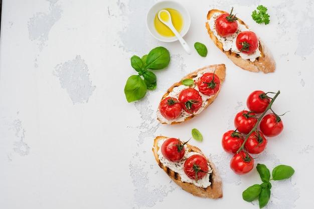 Сэндвич с запеченными помидорами черри, чесноком, оливковым маслом и творогом на белой поверхности