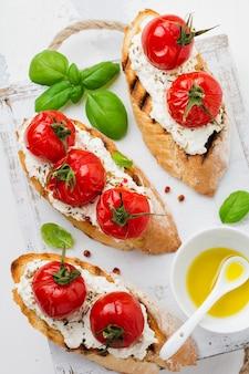 흰색 표면에 구운 체리 토마토, 마늘, 올리브 오일, 두부 치즈 샌드위치