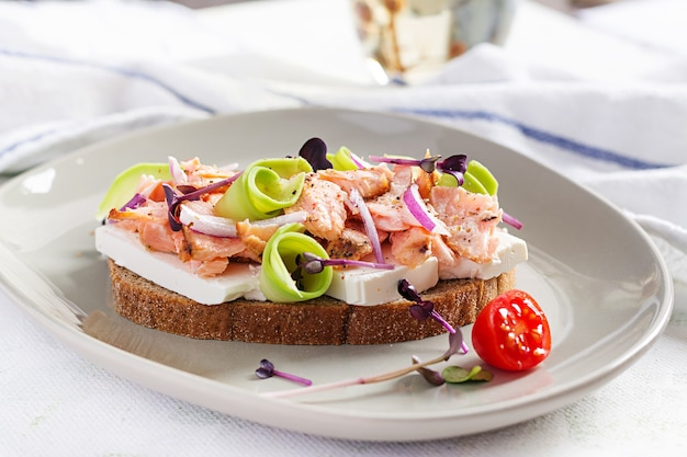 Sandwich with baked salmon, feta cheese, avocado and microgreens