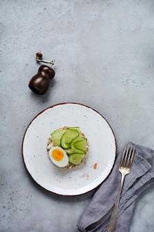 Сэндвич с вареным яйцом и огурцом на керамической тарелке на серой старой поверхности