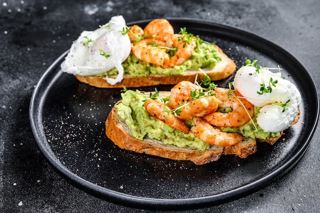 Sandwich with bread, avocado, shrimps, prawns and soft boiled egg. black background. top view