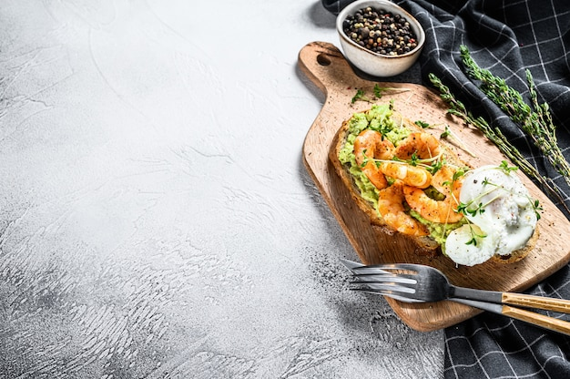 Sandwich with bread, avocado, shrimps, prawns and soft boiled egg. gray background. top view. copy space