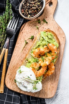 Sandwich with bread, avocado, shrimps, prawns and soft boiled egg. gray background. top view