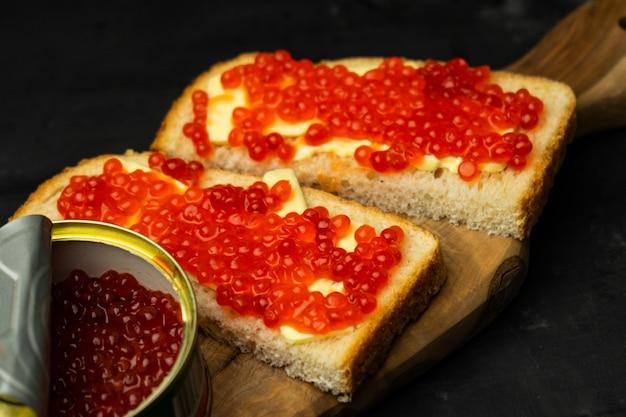 Бутерброд с маслом и красной икрой лосося на тестовом хлебе