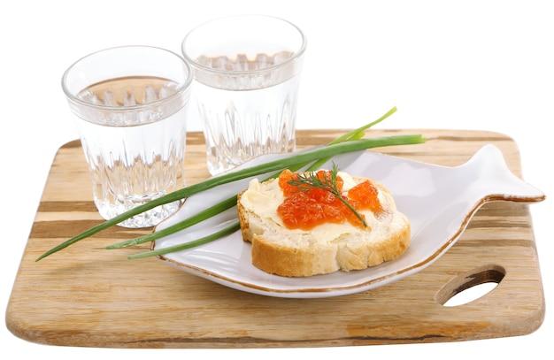 Бутерброд с икрой и водкой на деревянной доске, изолированные на белом фоне