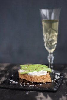 Sandwich with cheese and avocado, a glass of white wine