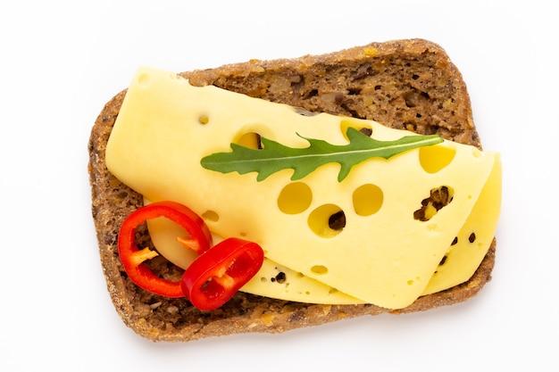 Бутерброд с сыром, листьями салата, помидорами, на белом фоне.