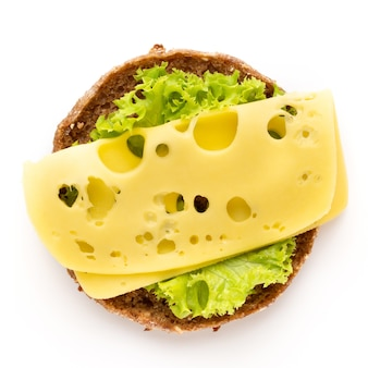 Sandwich with cheese, lettuce, tomato, on white background.