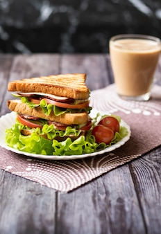 Sandwich with cheese, tomato, cucumber, sausage and lettuce on wood