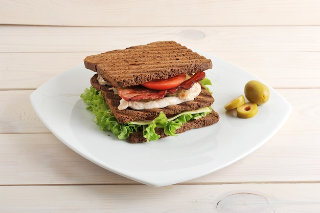 Sandwich with chicken and bacon on plate