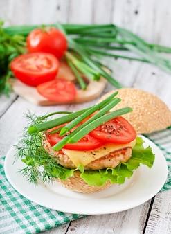 Бутерброд с куриным бургером, помидорами, сыром и листьями салата