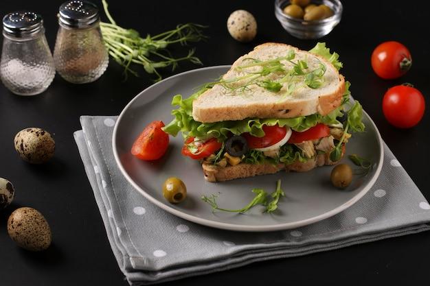 Сэндвич с курицей, помидорами черри, перепелиными яйцами и микрозеленью на темном фоне, крупным планом