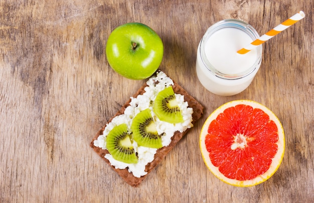 Sandwich with cottage cheese and slices of kiwi, grapefruit and yogurt.