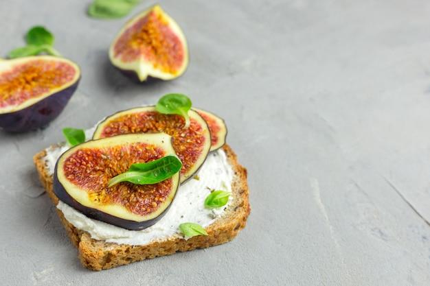 クリームチーズ、イチジク、蜂蜜、葉のサラダとサンドイッチは、灰色の木製の素朴なまな板で提供されます