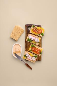 Сэндвич со сливочным сыром, помидорами и редисом на хрустящих тостах