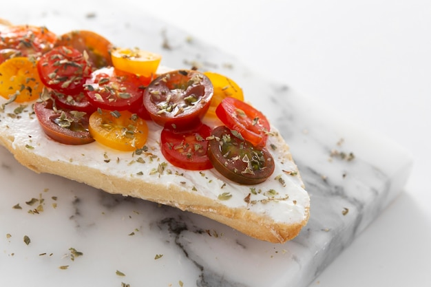 Sandwich with cream cheese and tomatoes on marble counter