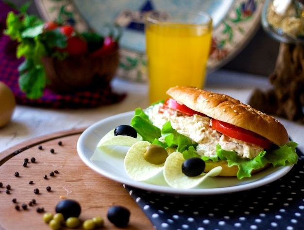 Sandwich with creamy salad and chips with olives